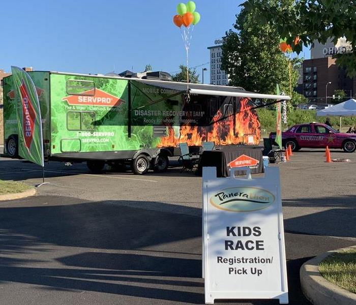SERVPRO Mobile Command Center with orange and green balloons with Kid's Race sign in front center