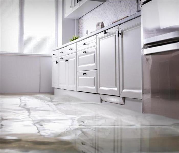 image of residential kitchen with clear standing water covering the floor of the room