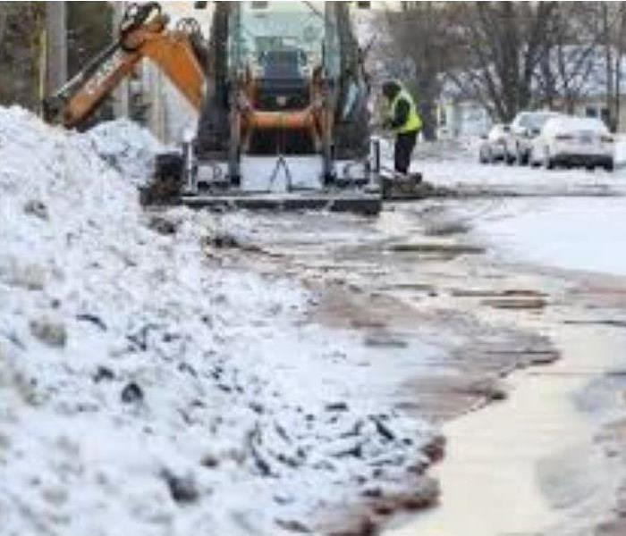 City workers tending to a water main break on the street in winter weather