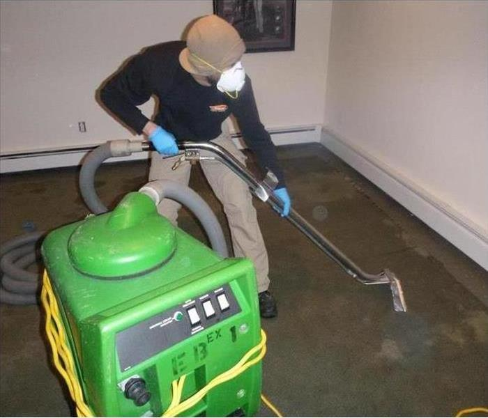 SERVPRO worker cleaning up water damage